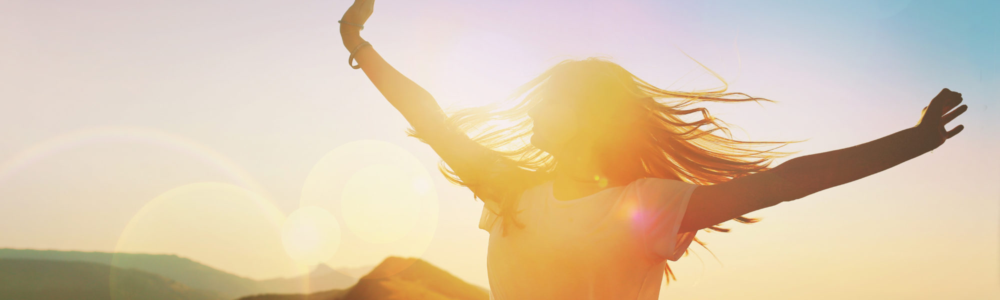 Girl on a background of mountains joyful spread her arms dancing at a height